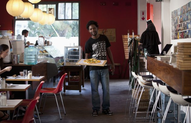 Terence Kamanda a waiter poses for a picture as he serves customers in The Corner Cafe restaurant in Durban