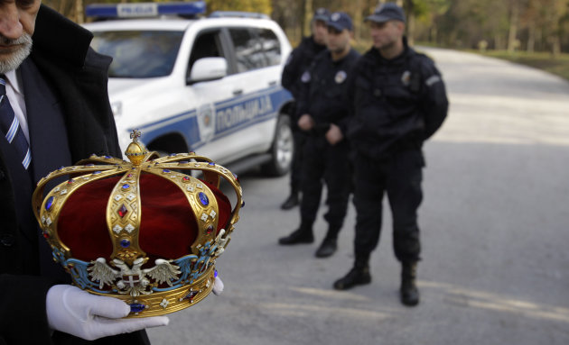 A man carries a crown of Peter II Karadjordjevic during a solemn ceremony after the remains of Yugoslavia's last king were flown back to Serbia in Belgrade, Serbia, Tuesday, Jan. 22, 2013. The former