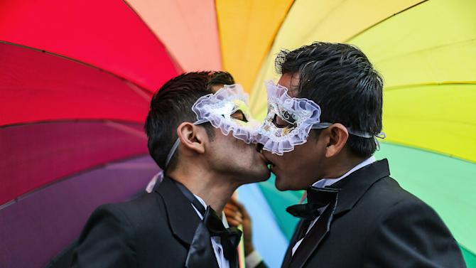 Men kiss under a rainbow umbrella during a gay pride parade in Lima, Peru, Saturday, June 28, 2014. Gays, lesbians and transgenders are holding gay pride parades worldwide this month as part of annual demonstrations demanding equal rights and to protest discrimination. (AP Photo/Sebastian Castaneda)