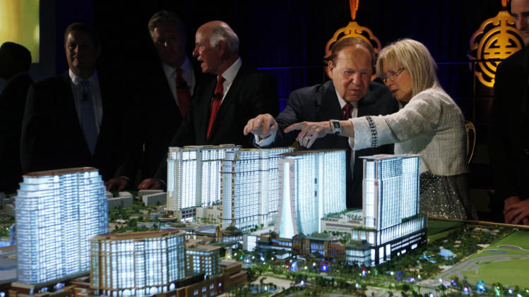 FILE - In this Wednesday, April 12, 2012 file photo, Las Vegas Sands Chairman and CEO Sheldon Adelson, second right, and his wife, Miriam Ochsorn, right, look at a model of the Sands Cotai Central resort during a news conference in Macau to announce the launch of the $4.4-billion complex, the company's latest bet on continued strong growth in the world's biggest gambling market. Adelson is giving tens of millions of dollars to Republican causes this election season, including a group supporting Mitt Romney. (AP Photo/Kin Cheung, File)