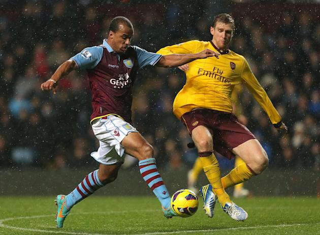 Gabriel Agbonlahor, left, is challenged by Per Mertesacker