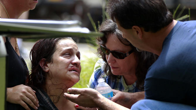 CORRECTS THAT DISABLED WOMAN IS THE DRIVER'S SISTER, NOT HER CHILD -  Passers-by comfort a woman after they rescued her from her burning car on Interstate 10 in Hancock County, Miss., Thursday, Aug. 16, 2012.   The fire was extinguished by the hose of a cement mixer, and fire extinguishers from nearby truckers. The woman was then extricated from the wreckage by the civilians as rescue personnel arrived, and she and her disabled sister, who was removed from the wreckage earlier, were airlifted from the scene. (AP Photo/Gerald Herbert)