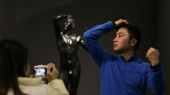 """A visitor poses for a photo in front of the sculpture """"The Bronze Age"""" by French artist Auguste Rodin at the National Museum of China in Beijing"""