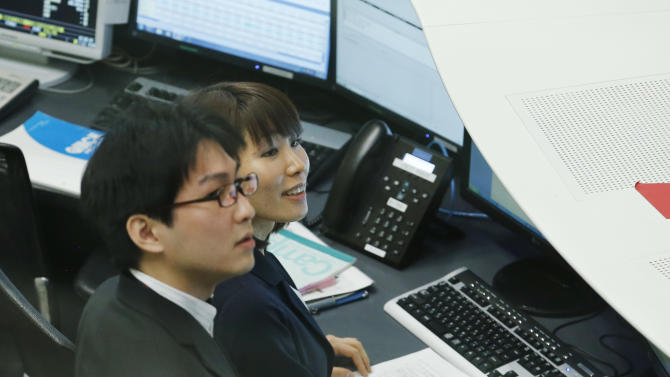 Workers of the Tokyo Stock Exchange react to the rise of the opening price at the first trading of the year on the Tokyo Stock Exchange in Tokyo, Friday, Jan. 4, 2013. (AP Photo/Koji Sasahara)