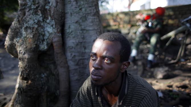In this photograph taken Friday Aug. 10, 2012, Ibrahim Nsanzimana, a 28-year-old Rwandan man, sits under a tree at the Congolese military intelligence offices in Goma, eastern Congo. Out of work and desperate to make a living, Nsanzimana agreed to join the Rwandan army in early July. After spending a week learning how to shoot with AK-47 assault rifles, he was told he was going to fight to take North Kivu province (of eastern Congo) and to make it part of Rwanda. Nsanzimana was captured three weeks ago by Congolese Tutsi soldiers.  (AP Photo/Jerome Delay)