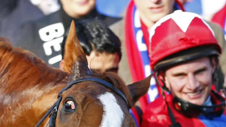 Jamie Moore poses for photographers with Sire De Grugy after they won the Queen Mother Champion Steeple Chase at the Cheltenham Festival horse racing meet in Gloucestershire