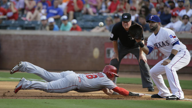 Los Angeles Angels Kole Calhoun (56) dives back to first base as Texas Rangers first baseman Mitch Moreland waits for the pick off throw during the first inning of a baseball game in Arlington, Texas, Sunday, July 5, 2015. (AP Photo/LM Otero)