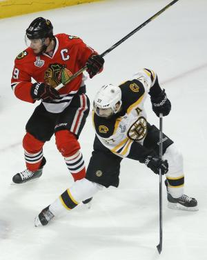Boston Bruins center Patrice Bergeron (37) looks for a rebound against Chicago Blackhawks center Jonathan Toews (19) in the first period during Game 5 of the NHL hockey Stanley Cup Finals, Saturday, June 22, 2013, in Chicago. Bergeron left the game in the second period with an injury and did not return. (AP Photo/Charles Rex Arbogast)