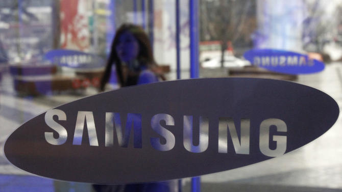 A woman stands behind a Samsung logo at Samsung Electronics Co. showroom inside its headquarters in Seoul, South Korea, Friday, Feb. 1, 2013. The chairman of Samsung Electronics has kept his fortune and control of the Samsung conglomerate after a South Korean court Friday ruled against his older brother in an inheritance battle. (AP Photo/Ahn Young-joon)