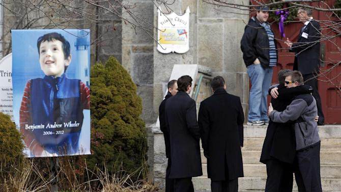 Mourners embrace outside of Trinity Episcopal Church while standing next to a portrait of Benjamin Andrew Wheeler, one of the students killed in the Sandy Hook Elementary School shooting last week, Thursday, Dec. 20, 2012, in Newtown, Conn. Wheeler, 6, died when the gunman, Adam Lanza, walked into Sandy Hook Elementary School in Newtown, Dec. 14, and opened fire, killing 26 people, including 20 children, before killing himself. (AP Photo/Julio Cortez)