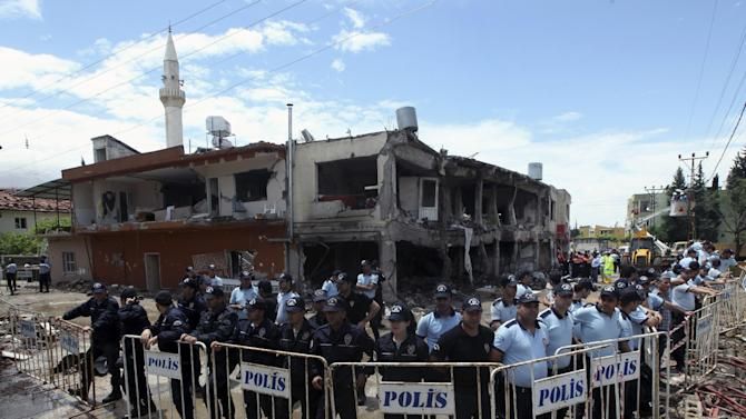 """Turkish riot police surround the destroyed shops two days after the explosions on Saturday that killed 46 and injured about 50 others, in Reyhanli, near Turkey's border with Syria, Monday, May 13, 2013. Prime Minister Recep Tayyip Erdogan said Monday Turkey would """"not refrain"""" from responding to twin car bombings it has blamed on Syria but also said it would also act with caution and not be drawn into its neighbor's civil war.  (AP Photo/Burhan Ozbilici)"""