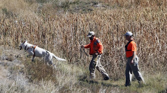 Members of a search and rescue team use a dog while searching for ten-year-old Jessica Ridgeway near her home in Westminster, Colo., on Monday, Oct. 8, 2012. The youngster has been missing since she left her home Friday morning on her way to school. (AP Photo/Ed Andrieski)
