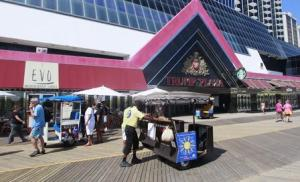People walk on the boardwalk in front of the Trump Plaza Hotel and Casino in Atlantic City