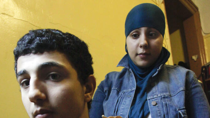 Janna Hakim, 18, and her brother Sulaiman Hakim, 17, shows a picture of their mother Faten on Thursday, Aug. 16, 2012 in New York.  On Aug. 13, 2010, Faten was taken away from home by ICE officials and deported to Ramallah, Palestine. (AP Photo/Bebeto Matthews)