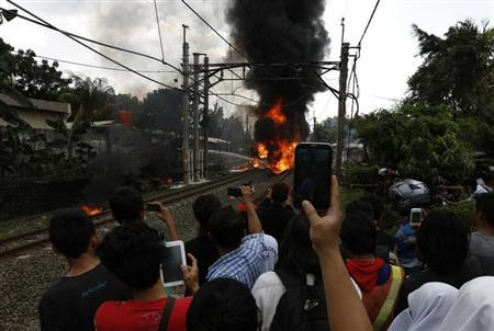 People take pictures of a burning commuter train after it collided at Bintaro district in Jakarta, December 9, 2013. REUTERS/Beawiharta