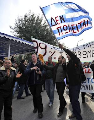 """An anti-austerity protester holds a Greek flag reading """"Not for sale'' before a scheduled military parade in the northern Greek city of Thessaloniki, Friday, Oct. 28, 2011. Thousands of anti-austerity protesters in this city forced the cancellation of Friday's annual military parade commemorating Greece's entry into World War II. The demonstrators heckled President Karolos Papoulias and other attending officials, calling Papoulias a traitor. (AP Photo/Nikolas Giakoumidis)"""
