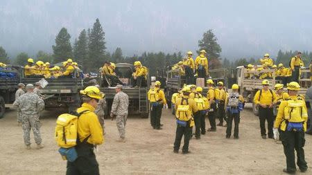 Washington State National Guard ground fire fighting personnel arrive to contain the Carlton Complex wildfire burning in North Central Washington