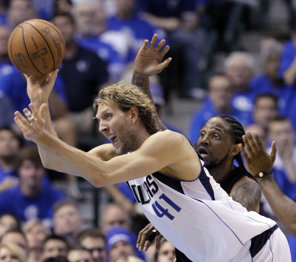 Dallas Mavericks' Dirk Nowitzki (41) passes the ball around Miami Heat's Udonis Haslem during the first half of Game 5 of the NBA Finals basketball game Thursday, June 9, 2011, in Dallas. (AP Photo/Mark Humphrey)