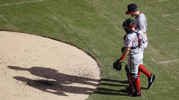 Washington Nationals catcher Ivan Rodriguez (7) talks to pitcher Stephen Strasburg (37) during the second inning of a baseball game against the Florida Marlins in Miami, Wednesday, Sept. 28 2011. (AP Photo/J Pat Carter)
