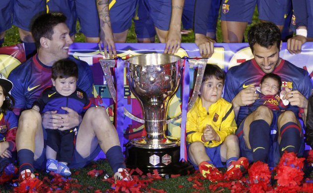Barcelona's Messi holds his son Thiago next to teammate Fabregas and his daughter Lia, as they pose with the trophy during celebrations at Camp Nou stadium in Barcelona