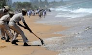Sri Lankan Coast Guard personnel clean up an oil slick washed up on the beach at the Wellawatte district of the capital Colombo on Saturday. An oil slick from a rusting cargo vessel that sank in bad weather reached the coast of Sri Lanka's capital on Saturday and threatened a beach resort popular with foreign tourists, officials said