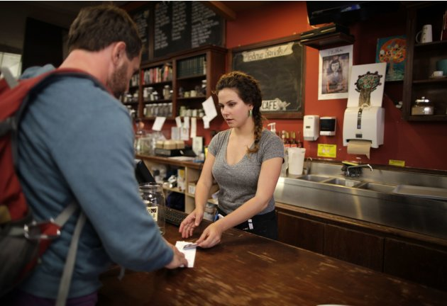Jessica Mazza, a 28 year-old waitress, serves a customer at Novel cafe in Santa Monica, California