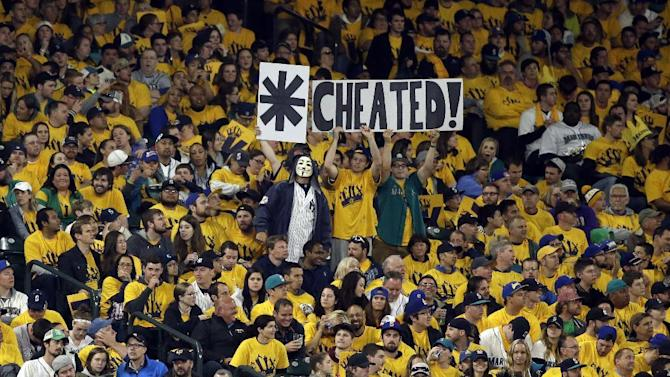Seattle Mariners' fans hold up signs to heckle New York Yankees' Alex Rodriguez as Rodriguez come to bat in a baseball game Monday, June 1, 2015, in Seattle. (AP Photo/Elaine Thompson)