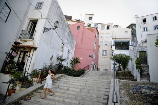 <p>A woman walks past houses in the Alfama neighborhood of Lisbon in August 2012. Portugal's public deficit is expected to reach 6.7 to 7.1 percent of output for the first half of this year, far off the government's target of 4.5 percent, experts commissioned by parliament said.</p>