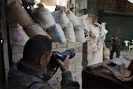 Japanese trucker Toshifumi Fujimoto takes pictures of a rebel fighter behind sandbags in Aleppo's old city on December 27, 2012. Dressed in Japanese army fatigues and armed with two cameras and a video camera -- Japanese, of course -- Fujimoto heads for whatever frontline he can every morning to document the ongoing destruction of Syria's second city and one-time commercial capital