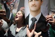 Syrian supporters of President Bashar al-Assad (portrait) chant pro-regime slogans in Damascus on May 7. Russia says President Bashar al-Assad could leave power as part of a settlement to end bloodshed in Syria, as Damascus agreed to allow relief workers to visit four trouble spots