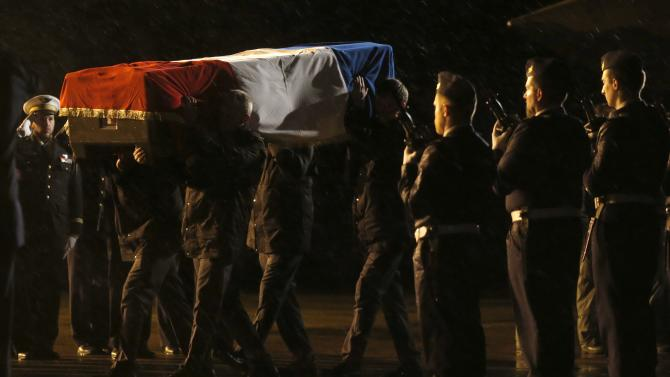 The flag-draped coffins of nine French Air Force personnel arrive at the Nancy-Ochey Airbase