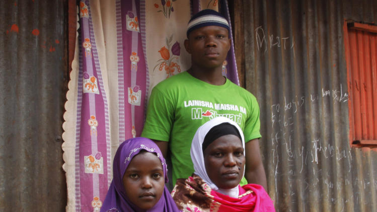 Latifah Naiman Mariki, widow of the late Haji Lukindo, with two of her children Juma Lukindo, 20, and Shamim Lukindo, 7, outside their house in Nairobi, Kenya, Friday, Aug. 2, 2013. An American diplomat who police say was speeding crossed the center line in his SUV and rammed into a full mini-bus, killing a father of three whose widow is six months pregnant, officials said Friday. Latifah Naiman Mariki, 38, and whose husband was killed in the crash, was almost evicted from her house this week after her landlord demanded rent. Mariki's deceased husband, Haji Lukindo, was the family's only source of income. Mariki told The Associated Press that neither the American driver nor anyone at the U.S. Embassy has contacted her, and she doesn't know how she will provide for her soon-to-be-born child and three children, ages 20, 10 and 7. (AP Photo/Khalil Senosi)