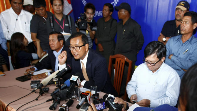 Cambodia National Rescue Party (CNRP) President Sam Rainsy, center, speaks during a press conference in his main party headquarters in Chak Angre Leu in Phnom Penh, Cambodia, Monday, July 29, 2013. Cambodia's opposition party CNRP said Monday it would challenge the results of a general election in which it made impressive gains even though the ruling party of Prime Minister Hun Sen retained power. (AP Photo/Heng Sinith)