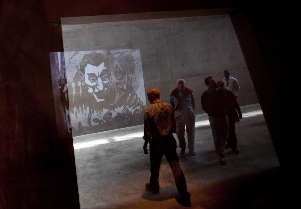 Visitors walk past as a film about anti-Semitism is seen reflected in the Yad Vashem Holocaust memorial in Jerusalem, Sunday, April 7, 2013. The annual Israeli memorial day for the 6 million Jews killed in the Holocaust of World War II begins at sundown Sunday. (AP Photo/Sebastian Scheiner)
