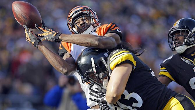Cincinnati Bengals wide receiver A.J. Green (18) is hit by Pittsburgh Steelers strong safety Troy Polamalu (43) as he tries to catch a pass in the second quarter of an NFL football game in Pittsburgh, Sunday, Dec 23, 2012. The pass was incomplete. (AP Photo/Gene J. Puskar)