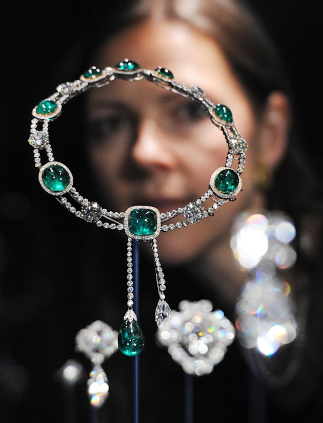 This Thursday June 28, 2012 photo shows curator Caroline de Guitaut, standing behind the Delhi Durbar Necklace and Cullinan Pendant made up of diamonds and emeralds, created for the Delhi Durbar of 19