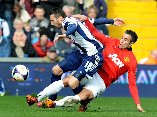 Manchester United's Robin van Persie tackles West Brom's Morgan Amalfitano during the English Premier League soccer match between West Bromwich Albion and Manchester United at The Hawthorns St