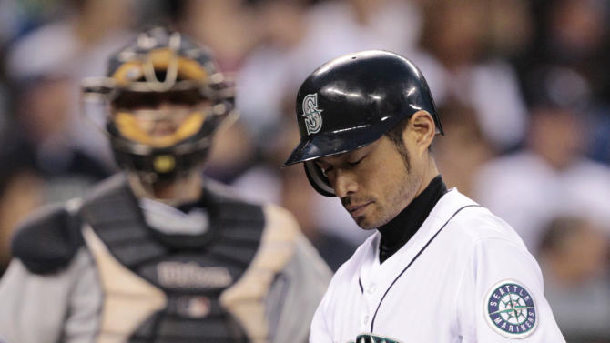 Seattle Mariners' Ichiro Suzuki looks over his broken bat as he turns to get a new one while San Diego Padres catcher Kyle Phillips looks on in the ninth inning in a baseball game Saturday, July 2, 2011, in Seattle. Suzuki grounded out on the turn. The Padres won 1-0. (AP Photo/Elaine Thompson)