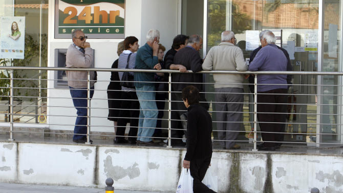 People wait outside a Coop Bank branch in Nicosia, Cyprus, Thursday, March 28, 2013. Cypriots get their first chance to access their savings in almost two weeks when the country's banks reopen Thursday - albeit with strict restrictions on transactions - after being closed due to the country's acute financial crisis. Lines were starting to form outside banks Thursday morning ahead of the official opening for six hours at noon (1000 GMT). (AP Photo/Philippos Christou)