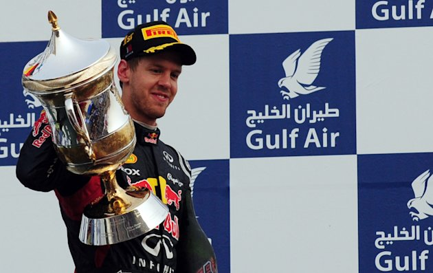 Red Bull Racing's German driver Sebastian Vettel poses on the podium with his trophy after winning the Bahrain Formula One Grand Prix in Manama on April 22, 2012. AFP PHOTO / Tom Gandolfini (Photo cre