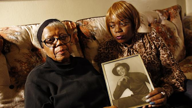 In this March 12, 2014 photo, Alma Murdough and her daughter Cheryl Warner hold a photo of Murdough's son, at her home in the Queens borough of New York. Jerome Murdough, a mentally ill, homeless former Marine arrested for sleeping in the roof landing of a New York City public housing project during one of the coldest recorded winters in city history, died last month in a Rikers Island jail cell that multiple city officials say was at least 100 degrees when his body was discovered. Murdough, 56, was found dead in his cell in a mental observation unit in the early hours of Feb. 15, after excessive heat, believed to be caused by an equipment malfunction, redirected it's flow to his upper-level cell, the officials said. (AP Photo/Jason DeCrow)