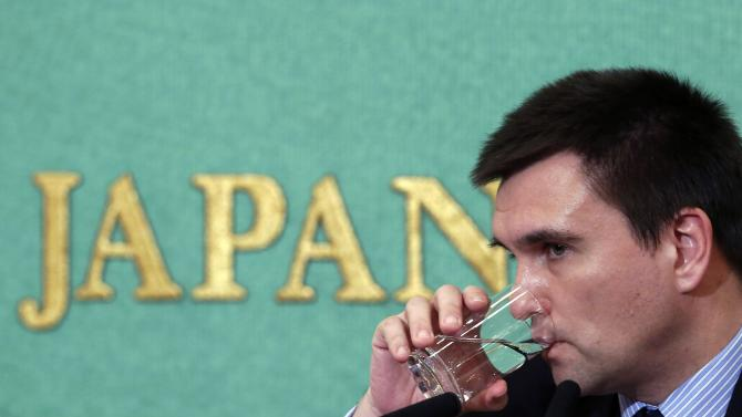Ukraine's Foreign Minister Pavlo Klimkin drinks a glass of water during a news conference in Tokyo