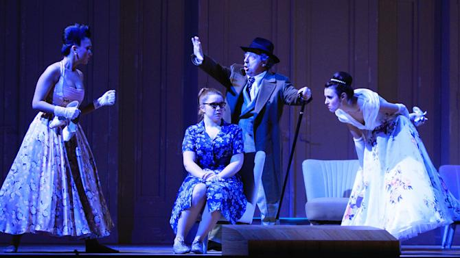 """FILE - In this Jan. 22, 2013 file photo Margarita Gritskova in the role of Tisbe, Tara Erraught as Angelina, Alessandro Corbelli as Don Magnifico and Valentina Nafornita as Clorinde, from left, perform during a dress rehearsal for the opera """"La Cenerentola"""" by Gioachino Rossini, at the state opera in Vienna, Austria. There is no pumpkin-turned-coach on the stage, no glass slipper, no fairy godmother, and the action takes place in an imaginary Italian duchy in the 1950s. But Gioachino Rossini's take on Cinderella remains utterly magical in the new version being put on by the Vienna State Opera with the premiere on Sunday Jan. 27, 2013. (AP Photo/dapd, Lilli Strauss,File)"""