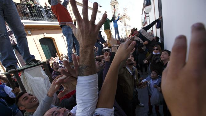 People wait to catch food thrown from balconies during the annual San Antonio Abad festival in Trigueros