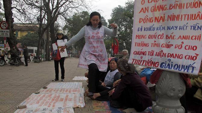 "Vietnamese women protest the seizure of their land by the government Thursday, Jan. 31, 2013 in Hanoi, Vietnam. Forced evictions are one of the main drivers of public anger against Vietnam's Communist leadership. Land disputes break out elsewhere in Asia, notably next door in China, but they have particular resonance in Vietnam, where wars and revolutions were fought in the name of the peasant class to secure collective ownership of the land.  A banner reads: ""People from provinces of An Giang, Binh Duong, Dong  Nai and Ninh Thuan who are filing their petitions, now spend all their money. We would like you to show your love to help us. We are waiting for the prime minister to solve.""  (AP Photo/Chris Brummitt)"