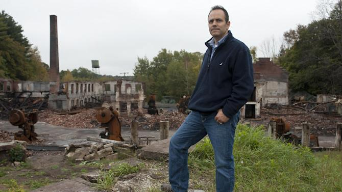 "Matt Bevin stands by the remains of his family's factory destroyed by fire in East Hampton, Conn., Wednesday, Oct. 3, 2012. The 180-year-old New England company that made the tiny bell that tinkles every time an angel gets its wings in the holiday classic ""It's a Wonderful Life"" is resuming production months after the factory was destroyed in a fire. (AP Photo/Jessica Hill)"