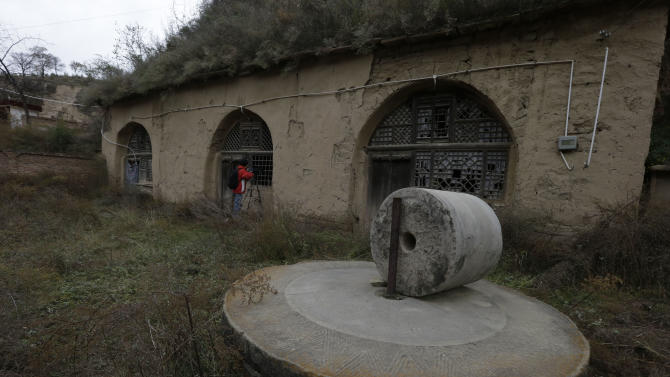 In this photo taken Thursday, Oct. 18, 2012, a cameraman shoots video of the cave dwelling where Chinese Vice President Xi Jinping used to live during his youth when he was sent to learn peasant virtues at Liangjiahe village in northwestern China's Shaanxi province. Xi, 59 and the country's vice president is expected to take over as head of the ruling party in November, 2012, before becoming president in 2013 of an increasingly assertive China. The Liangjiahe years are among scant details known about Xi's life and personality partly because he himself chronicled them as a key formative experience. (AP Photo/Ng Han Guan)