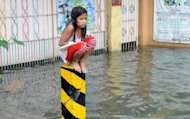 <p>A soaking wet child sits on a post on a flooded street in suburban Manila on August 8, 2012. Twenty people have died from this week's rains in Manila and nearby provinces, according to authorities.</p>
