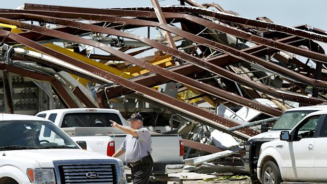 A police officer offers directions to a driver leaving this heavily damaged supply yard for Cactus Drilling Company on State Highway 66 in El Reno, Okla. on Saturday, June 1, 2013. Employee David Stottemyre was working in the lot when the tornado took aim at the plant. Stottemyre ran inside the large supply storage building and took shelter as the tornado passed over, leaving the building in a twisted pile of steel and metal. He was not injured. (AP Photo/The Oklahoman, Jim Beckel) LOCAL STATIONS OUT (KFOR, KOCO, KWTV, KOKH, KAUT OUT); LOCAL WEBSITES OUT; LOCAL PRINT OUT (EDMOND SUN OUT, OKLAHOMA GAZETTE OUT) TABLOIDS OUT