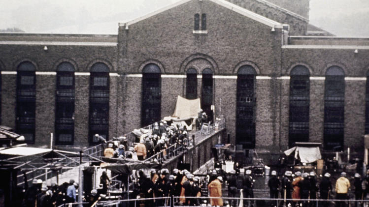 FILE - In this Sept. 13, 1971 file photo, prison guards and  New York State troopers gather outside Attica State Prison after retaking it from inmates who rioted and held the prison for five days, in Attica, N.Y. New York plans to seek the release of sealed court documents pertaining to the bloody retaking of Attica state prison after inmates rioted in 1971, an episode that remains the nation's bloodiest prison rebellion. Attorney General Eric Schneiderman said he'll ask a state court in Wyoming County to unseal previously secret documents containing details about the five days in September 1971 when inmates took control of the maximum-security prison in rural western New York before state troopers stormed the facility to end the takeover.  (AP Photo, File)